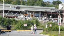 Lawyers for a public inquiry into the collapse of the Algo Centre Mall in Elliot Lake, Ont., lower left, visit the site on Tuesday, Aug. 14, 2012. The mall has been off-limits since part of it collapsed in June, killing two people. (Colin Perkel/The Canadian Press)