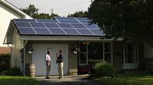 On the roof of his south Ottawa home, 33 solar panels are generating power for Samir Basaria which he sells to Ontario's electricity grid. He talks with David Cork from iSolara which installed the panels. (Blair Gable for the Globe and Mail)