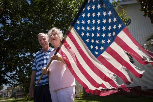 Caroline and Don McClure stand outside their home in New Orleans on July 16, 2015, holding their tattered American flag which survived Hurricane Katrina.