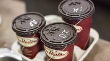 Coffee cups sit at a Tim Hortons in Oakville, Ont., in September, 2013. The coffee chain upped its revenue in the second quarter of 2014, though profits stayed flat. (Chris Young/The Canadian Press)