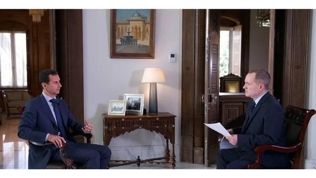 Syrian President Bashar Assad, left, speaks to Ian Phillips, vice-president of international news for Associated Press.