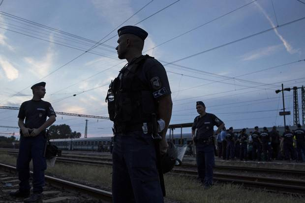 Police stand guard at the Bicske train station in Budapest.