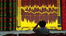 An investor looks at an electronic board showing stock information at a brokerage house in Hefei, Anhui province. (STRINGER SHANGHAI/REUTERS)