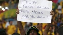 A Brazil fan waves a sign targeted at Brazil's coach Luiz Felipe Scolari before the 2014 World Cup third-place playoff between Brazil and the Netherlands at the Brasilia national stadium in Brasilia July 12, 2014. (JORGE SILVA/REUTERS)