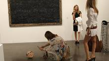 Adelaide Sutter of Switzerland, left, photographs a sculpture of former Italian prime minister Silvio Berlusconi by artist Kendell Geers, during the Vernissage Art Basel Miami Beach, Wednesday, Nov. 30, 2011, in Miami Beach, Fla. (Lynne Sladky/The Associated Press)