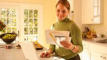 woman on laptop in kitchen paying bills (R. Michael Stuckey/Getty Images)