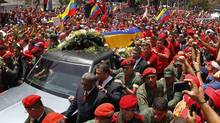 The coffin of deceased Venezuelan leader Hugo Chavez is driven through the streets of Caracas after leaving the military hospital where he died of cancer, in Caracas March 6, 2013. (Carlos Garcia Rawlins/Reuters)
