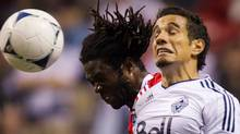 FC Dallas' Ugo Ihemelu, left, and Vancouver Whitecaps' Camilo Sanvezzo, of Brazil, jump for the ball during the second half of an MLS soccer game in Vancouver, B.C., on Saturday April 21, 2012. THE CANADIAN PRESS/Darryl Dyck (Darryl Dyck/CP)