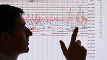 A seismologist poses for the media as he points to a seismographic graph showing the magnitude of the earthquake in Japan, on a monitor at the British Geological Survey office in Edinburgh, Scotland March 11, 2011. The biggest earthquake on record to hit Japan struck the northeast coast on Friday, triggering a 10-metre tsunami that swept away everything in its path, including houses, ships, cars and farm buildings. (DAVID MOIR/REUTERS/David Moir)