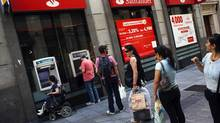 People line up as they wait to use ATM machines at a branch of Spain's largest bank Santander in central Madrid. (SUSANA VERA/REUTERS)