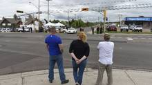 Moncton residents gather to watch police officers and the media near a roadblock in northern Moncton, Thursday, June 5, 2014. (Fred Lum/The Globe and Mail)