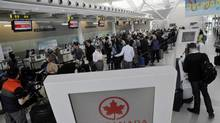 Passengers wait in line for an Air Canada flight at Toronto's Pearson airport, March 18, 2012. (J.P. MOCZULSKI For The Globe and Mail)