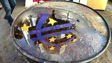 The Euro sculpture is reflected in a puddle on the lid of a bin that stands in the Frankfurt Occupy camp at the European Central Bank in Frankfurt, Germany, Wednesday, Nov.30, 2011 (Michael Probst/AP)