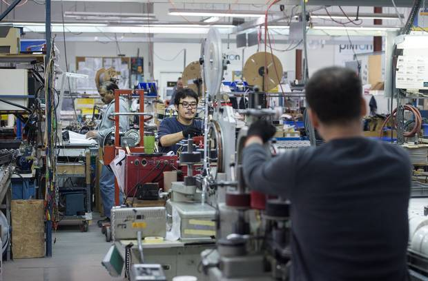 Workers are seen at Toronto's Plitron Manufacturing Inc. on Nov. 2, 2015.