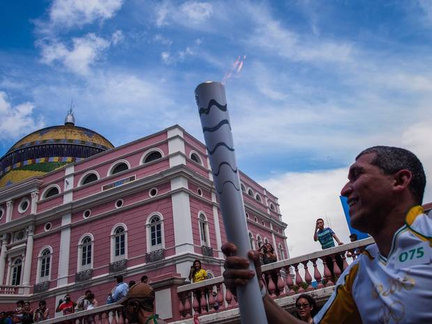 Euler Ribeiro Filho, carries the Olympic torch upon arrival in Manaus in front of the Amazon Theatre.