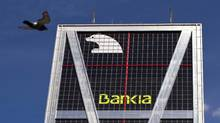 A bird flies past the headquarters of Bankia bank in Madrid June 11, 2012. Euro zone finance ministers agreed on Saturday to lend Spain up to €100-billion ($125-billion U.S.) to shore up its teetering banks and Madrid said it would specify precisely how much it needs once independent audits report in just over a week. Spain's biggest failed bank, Bankia , will cost €23.5-billion to rescue and its shareholders have been wiped out. (Paul Hanna/REUTERS)