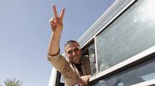 A Palestinian prisoner, released by Israel in exchange for Israeli soldier Gilad Shalit, gestures from a bus as he makes his way through the Rafah border crossing between Egypt and Gaza October 18, 2011. (ANDREW WINNING/Andrew Winning/Reuters)