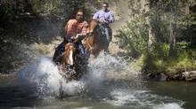 Jimmy Lulua and Chief Roger William splashe through a river during the first heat of the mountain race at Nemiah Valley Rodeo August 4, 2012. (John Lehmann/The Globe and Mail)