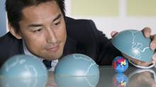 Businessman playing with globes (Comstock Images)