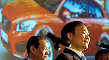 Li Shufu, right, chairman of Chinese automaker Geely, speaks while a photo of a Volvo car is projected on a screen during a press conference in Beijing March 30, 2010. Zhejiang Geely Holding Group expects to spend hundreds of millions of dollars beyond the US$1.8 billion purchase price for Volvo Cars to make the Swedish car company profitable, Li said. (Alexander F. Yuan/Alexander F. Yuan/AP)