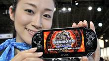 "A model displays Sony Computer Entertainment's new portable videogame console ""PlayStation Vita"", while visitors try it out at the annual Tokyo Game Show in Chiba, suburban Tokyo on September 15, 2011. Sony will release its next-generation PS Vita in Japan on December 17. (YOSHIKAZU TSUNO/AFP/Getty Images)"