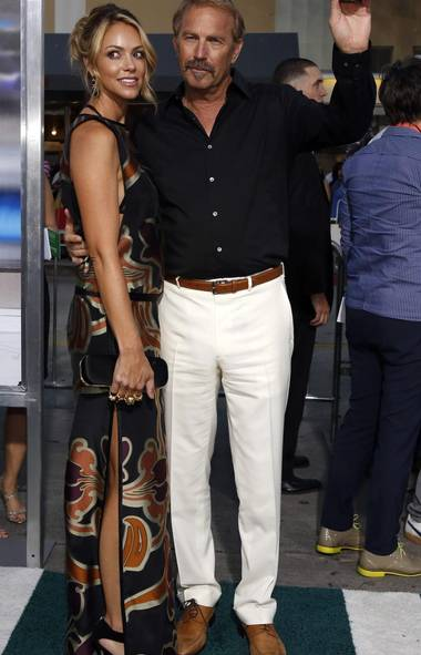 Who says there are no real movie stars in Hollywood today? Because it's true. Here's sixtysomething Kevin Costner, with trophy wife Christine at the premiere of his new movie Draft Day in Los Angeles. Dude, we can take the bronzer and hair transplants, but even when white pants were in they weren't in (MARIO ANZUONI/REUTERS)