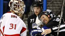 Tampa Bay Lightning's Dominic Moore (R) is grabbed by Ottawa Senators' Chris Neil after scoring against goalie Curtis McElhinney (L) as teammate Victor Hedman (77) looks on during the second period of an NHL hockey game in Tampa, Florida March 29, 2011. REUTERS/Mike Carlson (MIKE CARLSON)