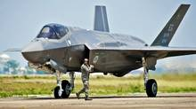 A maintenance worker checks a U.S. Air Force F-35 Lightning II fighter jet at Florida's Eglin Air Force on July 14, 2011. (Samuel King Jr./AP)