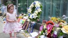 Three year-old Rebecca Brown walks past a memorial to deceased actor Cory Monteith outside the Fairmont Pacific Rim Hotel in Vancouver, British Columbia, Canada July 16, 2013. (Jeff Vinnick/The Globe and Mail)