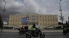 Protesters with motorcycles and a Greek flag pass in front of Greek parliament during a demonstration in Athens on Dec. 19, 2012. Civil servants in Greece staged a 24-hour strike as thousands gathered in protest against new austerity measures that will see more pay cuts next year as well as a rare round of job cuts. (Dimitri Messinis/Associated Press)