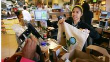 Cashier Michelle Yulo hands out free reusable grocery bags at a Whole Foods Market natural and organic foods stores which is ending the use of disposable plastic grocery bags in its 270 stores in the US, Canada and UK on Earth Day, April 22, 2008 in Pasadena, Calif. (David McNew/2008 Getty Images)