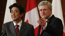 Prime Minister Stephen Harper, right, gestures at the conclusion of a news conference with his Japanese counterpart Shinzo Abe on Parliament Hill in Ottawa on Sept. 24, 2013. Mr. Harper says he will encourage diplomatic efforts to settle the Iranian nuclear question, but he warns that Iran must be judged by deeds, not words. (CHRIS WATTIE/REUTERS)