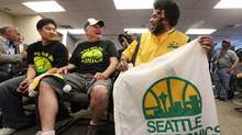 Seattle SuperSonics supporters Joseph Chong, left, David Brown, center, and Kris Brannon share a laugh as they wait for a news conference to begin Wednesday, May 16, 2012, in Seattle. (Elaine Thompson/AP/Elaine Thompson/AP)