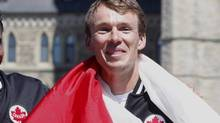 Triathlete Simon Whitfield is wrapped in the Canadian Flag after he was named the official flag bearer for Canada at the 2012 London Olympics, on Parliament Hill, Thursday July 12 2012 in Ottawa. (FRED CHARTRAND/THE CANADIAN PRESS)