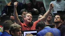 A trader signals an offer in the Chicago Board Options Exchange on Wednesday. Markets responded enthusiastically as the world's major central banks stepped in to ensure capital keeps flowing. Stocks soared to their highest level since August. (Scott Olson/Getty Images)