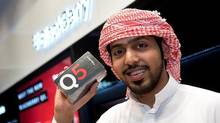 Hamad Majed Alabbar from Qatar shows off his new Q5 BlackBerry in Dubai. RIM reports earnings on Friday. (Research In Motion)