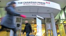 Pedestrians walk past The Canadian Press head office entrance in Toronto (Graeme Roy/THE CANADIAN PRESS)