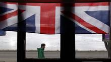 A man is seen from a window with the Union Jack hung as he walks on Ross road in Stanley, March 11, 2013. Residents of the Falkland Islands started voting on Sunday and continue Monday in a sovereignty referendum that seeks to counter Argentina's increasingly assertive claim over the British-ruled territory. (MARCOS BRINDICCI/REUTERS)
