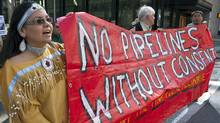 Members of the Yinka Dene Alliance march through downtown Calgary on May 11, 2011 to protest against Enbridge's proposed Northern Gateway pipeline project. (Jeff McIntosh/Jeff McIntosh/The Canadian Press)