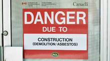 A danger sign is seen outside a construction zone in Ottawa laden with asbestos on June 20, 2011. (Adrian Wyld/THE CANADIAN PRESS)