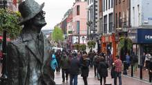 A statue of author James Joyce overlooks shoppers on Dublin's North Earl Street. Ireland's government will on Thursday re-enter the bond market, the first time since September, 2010. (Shawn Pogatchnik/AP)