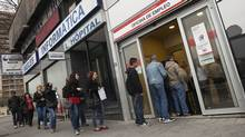 People enter a government employment office in Madrid April 3, 2012. Spain's number of registered jobless rose for the eighth straight month in March. (© Juan Medina / Reuters/JUAN MEDINA/REUTERS)