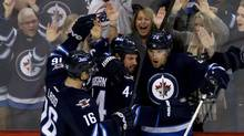 Winnipeg Jets' Andrew Ladd, left to right, Zach Bogosian and Blake Wheeler celebrate Wheeler's goal against the Boston Bruins' during third period NHL action in Winnipeg, Tuesday, March 19, 2013. (Trevor Hagan/THE CANADIAN PRESS)