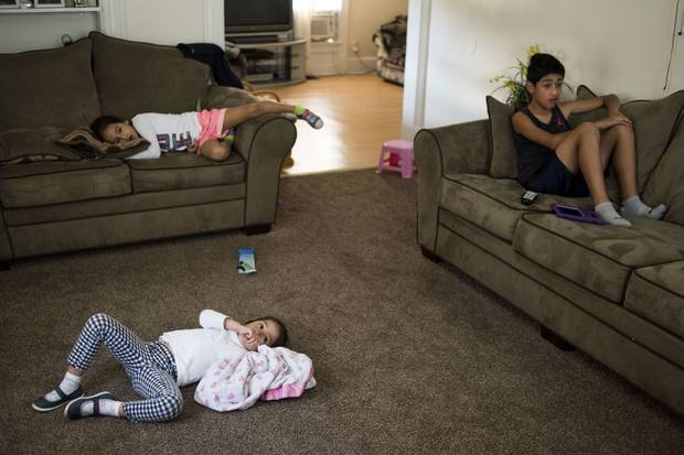 Mackaylah, Evelyn and Anthony watch TV in their living room.