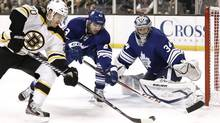 Boston Bruins' Daniel Paille looks for a shot against Toronto Maple Leafs goalie James Reimer and teammate Nazem Kadri during the second period of an NHL hockey game in Boston Monday, March 25, 2013. (Winslow Townson/AP)