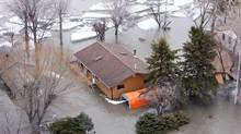 Homes and Cottages along Provincial Road 320 are flooded and risk being damaged by large slabs of ice moving along the Red River after north of Selkirk, Man., on April 12, 2009. (Ruth Bonneville)