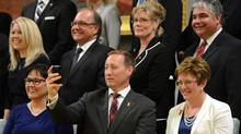 Canada's Justice Minister Peter MacKay takes a picture of photographers and cameramen while posing with fellow cabinet ministers during a swearing-in ceremony at Rideau Hall in Ottawa July 15, 2013. (Chris Wattie/REUTERS)