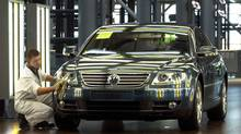 An employee polishes a Volkswagen Phaeton in the factory, Glaeserne Manufaktur, in Dresden, eastern Germany, Thursday, Aug. 22, 2002, while the car stands in a tunnel for a paintwork quality check. (MATTHIAS RIETSCHEL/AP Photo)