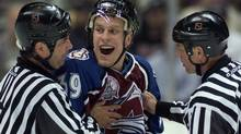 File - Linesman Dan Schacte (L) and referee Dan Marouelli (R) hold back Colorado Avalanche's Ville Nieminen as he argues a boarding penalty during the first period against the New Jersey Devils in Game 3 of the NHL Stanley Cup Finals in East Rutherford, May 31, 2001. REUTERS/Mike Segar (MIKE SEGAR)