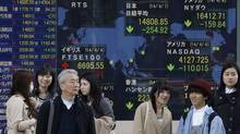 Pedestrians stand in front of an electronic stock price indicator in Tokyo on April 7, 2014. Internet and technology stocks tumbled across Asia as a sell-off spread from Wall Street. (Shizuo Kambayashi/AP)